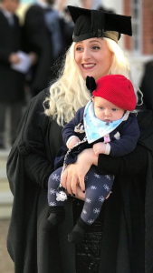 A woman wearing graduating robes and mortar board smiles and holds a baby who wears a red hat