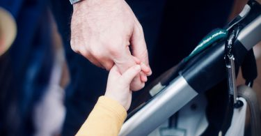 A child's hand holds the index finger of a man. In between the two is the handle of a pushchair